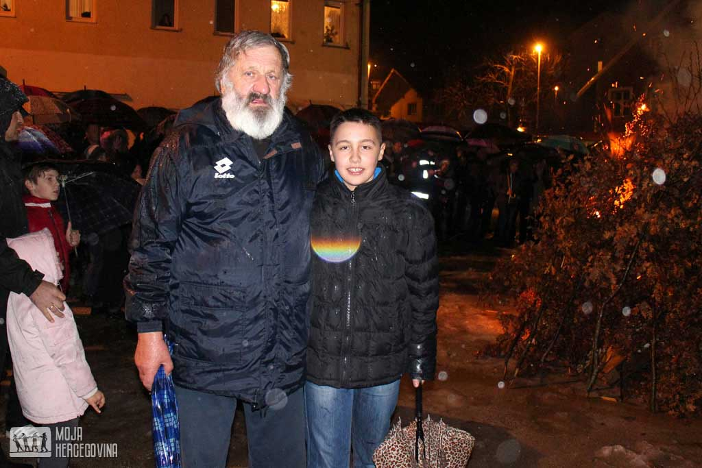 Kiša nije spriječila Radojicu Boškovića da sa unukom prisustvuje nalaganju badnjaka (FOTO: Moja Hercegovina)